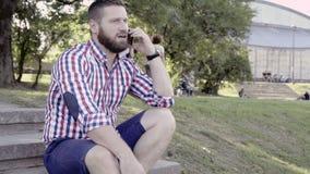 Άτομο που μιλά από το smartphone, που κάθεται στα σκαλοπάτια Ολισθαίνων ρυθμιστής και παν πυροβολισμός απόθεμα βίντεο
