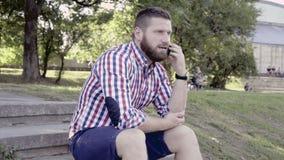Άτομο που μιλά από το smartphone, που κάθεται στα σκαλοπάτια πυροβολισμός ολισθαινόντων ρυθμιστών απόθεμα βίντεο