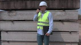 Άτομο που μιλά στους walky talky κοντινούς φραγμούς κατασκευής απόθεμα βίντεο