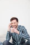 Άτομο που μιλά στο κινητό τηλέφωνο που κρατά ένα φλυτζάνι του τσαγιού Στοκ εικόνα με δικαίωμα ελεύθερης χρήσης