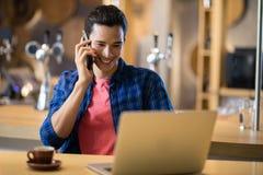 Άτομο που μιλά στο κινητό τηλέφωνο χρησιμοποιώντας το κινητό τηλέφωνο στο εστιατόριο Στοκ Εικόνες