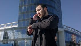 Άτομο που μιλά στο τηλέφωνο και που κοιτάζει στο ρολόι του απόθεμα βίντεο