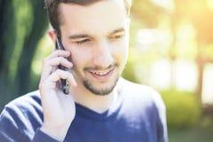 Άτομο που μιλά στο τηλέφωνο στην ηλιόλουστη ημέρα στοκ εικόνες
