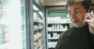 Άτομο που μιλά στο τηλέφωνο στο κατάστημα τροφίμων απόθεμα βίντεο