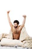 Άτομο που ξυπνά στο κρεβάτι και που τεντώνει τα όπλα του Στοκ φωτογραφία με δικαίωμα ελεύθερης χρήσης