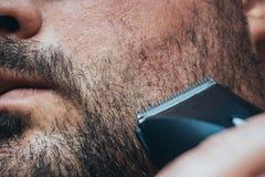 Άτομο που ξυρίζει τη σκληρή τρίχα του με τον κουρευτή ζώων τρίχας ή ηλεκτρικό trimmer Προσοχή γενειάδων και κατάστημα κουρέων στοκ φωτογραφία