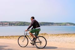 Άτομο που οδηγά ένα ποδήλατο στο ανάχωμα της αδριατικής θάλασσας στο ψ στοκ εικόνα με δικαίωμα ελεύθερης χρήσης