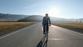 Άτομο που οδηγά ένα ποδήλατο στο δρόμο ασφάλτου προς την ηλιόλουστη δεκαετία του '20 ουρανού ηλιοβασιλέματος 4k απόθεμα βίντεο