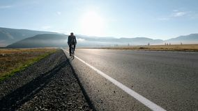 Άτομο που οδηγά ένα ποδήλατο στο δρόμο ασφάλτου προς την ηλιόλουστη δεκαετία του '20 ουρανού ηλιοβασιλέματος 4k φιλμ μικρού μήκους