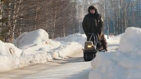 Άτομο που οδηγούν στο μίνι όχημα για το χιόνι αντιολισθητικών αλυσίδων με ένα ρυμουλκό και ένας επιβάτης σε έναν χειμερινό δρόμο απόθεμα βίντεο
