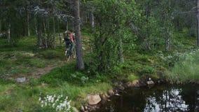 Άτομο που οδηγά ένα ποδήλατο σε έναν δασικό πυροβολισμό κηφήνων απόθεμα βίντεο