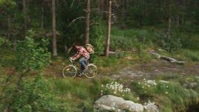 Άτομο που οδηγά ένα ποδήλατο σε έναν δασικό πυροβολισμό κηφήνων φιλμ μικρού μήκους