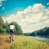 Άτομο που οδηγά ένα ποδήλατο στην όχθη ποταμού ενάντια ανασκόπησης μπλε σύννεφων πεδίων άσπρο σε wispy ουρανού φύσης χλόης πράσιν Στοκ Φωτογραφία