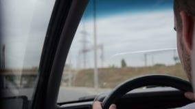 Άτομο που οδηγεί ένα αυτοκίνητο κατά μια πίσω άποψη απόθεμα βίντεο