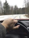 Άτομο που οδηγεί ένα αυτοκίνητο σε έναν χιονώδη δρόμο Ο έλεγχος έλξης είναι κλειστός Στοκ Φωτογραφία