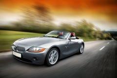 Άτομο που οδηγεί τη BMW Z4 γρήγορα στο δρόμο καρστ Στοκ Εικόνες
