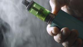 Άτομο που ο ηλεκτρονικός νεαρός δικυκλιστής τσιγάρων, σύννεφα του καπνού ατμού, κινηματογράφηση σε πρώτο πλάνο απόθεμα βίντεο