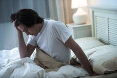 Άτομο που πάσχει από τον πονοκέφαλο στο κρεβάτι Στοκ Εικόνες