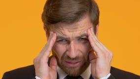 Άτομο που πάσχει από το φοβερό πονοκέφαλο, που απομονώνεται στο πορτοκαλί υπόβαθρο, κινηματογράφηση σε πρώτο πλάνο απόθεμα βίντεο