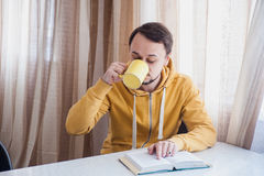 Άτομο που πίνει τον καυτό καφέ και την ανάγνωση Στοκ Εικόνες