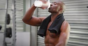 Άτομο που πίνει το πρωτεϊνικό κούνημα στη γυμναστική crossfit απόθεμα βίντεο