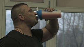 Άτομο που πίνει το πρωτεϊνικό κούνημα στη γυμναστική crossfit φιλμ μικρού μήκους