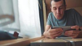 Άτομο που παίζει ένα παιχνίδι online σε ένα smartphone, ισχυρές συγκινήσεις, συνεδρίαση ατόμων θυμού σε ένα τραίνο από το παράθυρ φιλμ μικρού μήκους