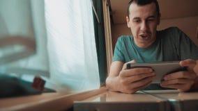 Άτομο που παίζει ένα παιχνίδι online σε ένα smartphone, ισχυρές συγκινήσεις, συνεδρίαση ατόμων θυμού σε ένα τραίνο από το παράθυρ απόθεμα βίντεο