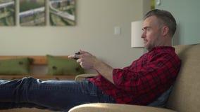 Άτομο που παίζει με προσήλωση ένα τηλεοπτικό παιχνίδι σε έναν καναπέ φιλμ μικρού μήκους