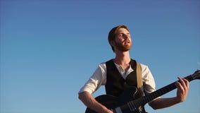 Άτομο που παίζει σόλο την κιθάρα και που απολαμβάνει τη μουσική απόθεμα βίντεο