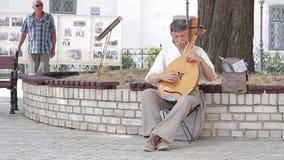 Άτομο που παίζει την άρπα στο προαύλιο της εκκλησίας φιλμ μικρού μήκους
