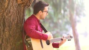 Άτομο που παίζει την ακουστική κιθάρα που κλίνει ενάντια σε ένα δέντρο απόθεμα βίντεο