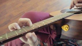 Άτομο που παίζει την ακουστική κινηματογράφηση σε πρώτο πλάνο κιθάρων σε αργή κίνηση φιλμ μικρού μήκους