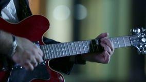 Άτομο που παίζει την κόκκινη κιθάρα στη νύχτα απόθεμα βίντεο
