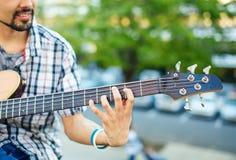 Άτομο που παίζει τη βαθιά ακουστική κινηματογράφηση σε πρώτο πλάνο κιθάρων Στοκ Φωτογραφία