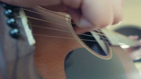 Άτομο που παίζει τις ακουστικές σειρές κινηματογραφήσεων σε πρώτο πλάνο κιθάρων σε αργή κίνηση φιλμ μικρού μήκους