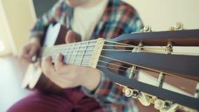 Άτομο που παίζει το ακουστικό υπόβαθρο κιθάρων σε αργή κίνηση φιλμ μικρού μήκους