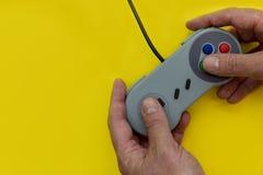 Άτομο που παίζει το τηλεοπτικό παιχνίδι με το κίτρινο υπόβαθρο ελεγκτών στοκ εικόνες με δικαίωμα ελεύθερης χρήσης