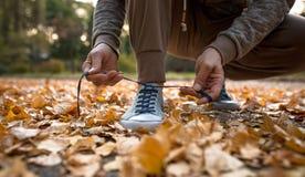 Άτομο που παίρνει έτοιμο για το τρέξιμο των αθλητικών παπουτσιών δεσίματος Στοκ φωτογραφία με δικαίωμα ελεύθερης χρήσης