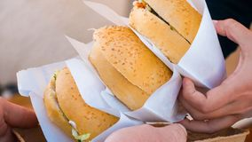 Άτομο που παίρνει τα burgers στο φεστιβάλ τροφίμων οδών στοκ φωτογραφία