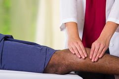 Άτομο που παίρνει τη φυσική επεξεργασία ποδιών από το φυσιο θεράποντα, τα χέρια της που εργάζεται στους μόσχους του που εφαρμόζου Στοκ Φωτογραφία
