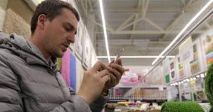 Άτομο που παίρνει τη φωτογραφία στο οικιακό τμήμα της υπεραγοράς απόθεμα βίντεο
