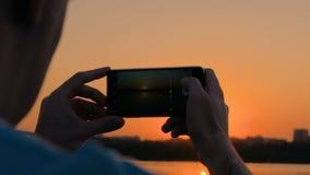 Άτομο που παίρνει τη φωτογραφία του ηλιοβασιλέματος με το smartphone στην αποβάθρα πόλεων απόθεμα βίντεο