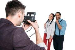 Άτομο που παίρνει τη φωτογραφία του νέου ζεύγους αφροαμερικάνων με τη στιγμιαία εκλεκτής ποιότητας κάμερα Στοκ φωτογραφία με δικαίωμα ελεύθερης χρήσης