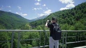 Άτομο που παίρνει τη φωτογραφία των βουνών φιλμ μικρού μήκους
