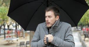 Άτομο που παίρνει το κρύο περπάτημα το χειμώνα κάτω από τη βροχή απόθεμα βίντεο