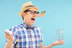 Άτομο που παγιδεύει μια πεταλούδα σε ένα βάζο Στοκ Φωτογραφίες