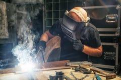 Άτομο που παρασκευάζει μια μηχανή συγκόλλησης μετάλλων Στοκ Φωτογραφίες