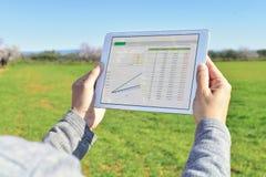 Άτομο που παρατηρεί μερικά διαγράμματα σε μια ταμπλέτα σε έναν τομέα αγραναπαύσεων Στοκ φωτογραφία με δικαίωμα ελεύθερης χρήσης