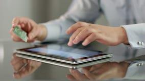 Άτομο που παρεμβάλλει το αριθμό πιστωτικής κάρτας στο PC ταμπλετών, σε απευθείας σύνδεση τραπεζικές εργασίες απόθεμα βίντεο